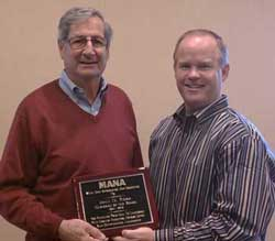 MANA Chairman of the Board Tom Hayward presents a plaque to John Roba (left)